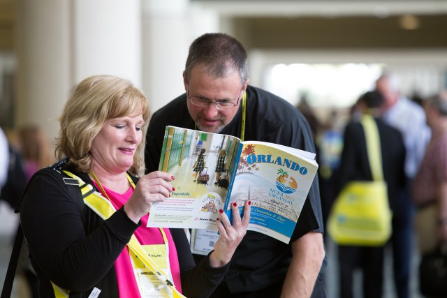 Attendees check the program schedule April 7 during the annual convention of the National Catholic Educational Association. Some 5,000 took part in the three-day event. (CNS/Tom Tracy)