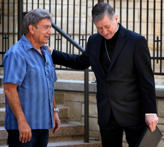 Chicago Archbishop Blase J. Cupich talks to Cardinal Francis E. George's barber, Alfredo Fricaso, in front of Holy Name Cathedral April 17, prior to announcing the death of the cardinal. (CNS/Karen Callaway, Catholic New World)