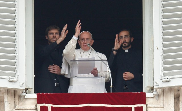 Pope Francis and two newly ordained priests give a blessing during the