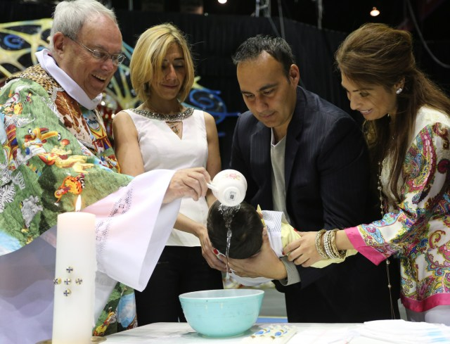 Priest baptizes child during Mass in center ring of Ringling Bros. and Barnum & Bailey Circus at university in Virginia