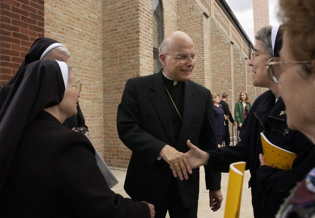 Cardinal Francis George greets people in 2003 following Mass in celebration of the 100th Anniversary of St. George's Church in Chicago. Cardinal George, 78, died April 17 after a long battle with cancer. (CNS photo/ Karen Callaway)