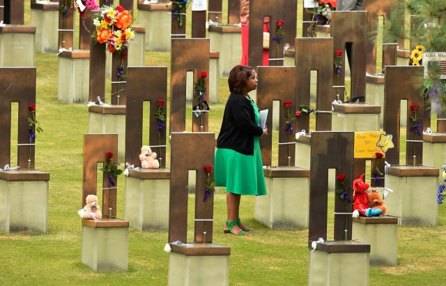 A woman stands in the middle of the 168 chairs representing the dead at the Oklahoma City National Memorial & Museum April 19.  (CNS/Larry W. Smith, EPA)