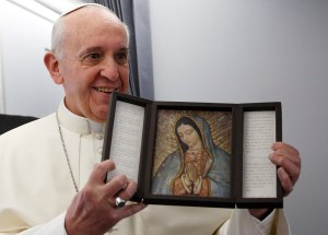 Pope Francis holds an image of Our Lady of Guadalupe aboard the papal flight to Brazil in 2013. The pope is deeply devoted to Mary. (CNS/Paul Haring)