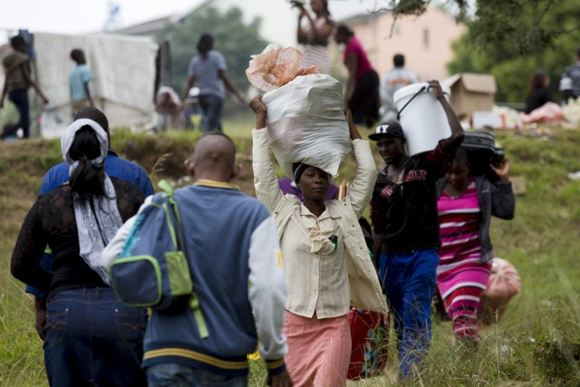 Zimbabwe nationals carry their bags before boarding a bus home from a camp for those affected by anti-immigrant violence near Durban, South Africa, April 19. Attacks on foreign nationals, which have left at least seven people dead and more than 5,000 displaced, started in Durban in early April and spread to other parts of the country. (CNS/Rogan Ward, Reuters)