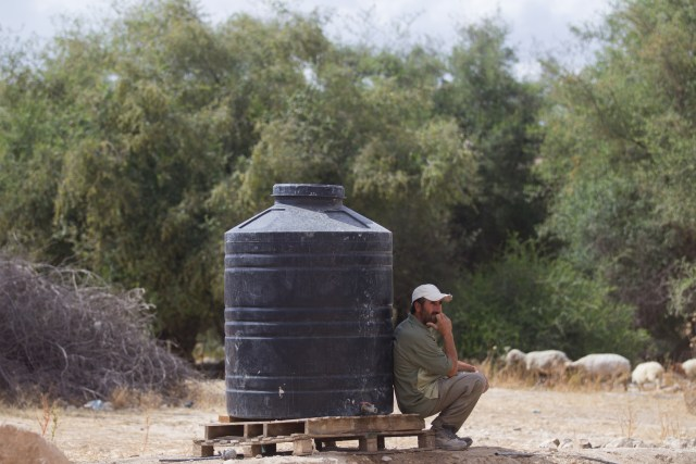 A Palestinian man leans up against a water tank in Fasayel, West Bank. (CNS photo/Miriam Alster)