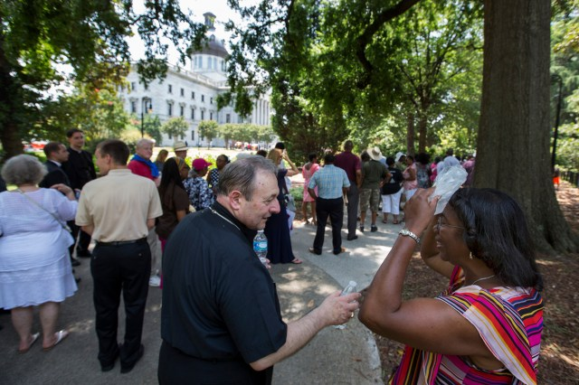 Bishop Robert E. Guglielmone of Charleston, S.C., talks to Barbara Thompson of Manning, S.C., while she waits in the heat outside the South Carolina Statehouse in Columbia June 24. Inside the Capitol the body of the Rev. Clementa C. Pinckney, a pastor and state senator, lay in state. The pastor of Emanuel African Methodist Episcopal Church in Charleston was one of nine people shot and killed at the church June 17. (CNS/Mic Smith, The Catholic Miscellany)