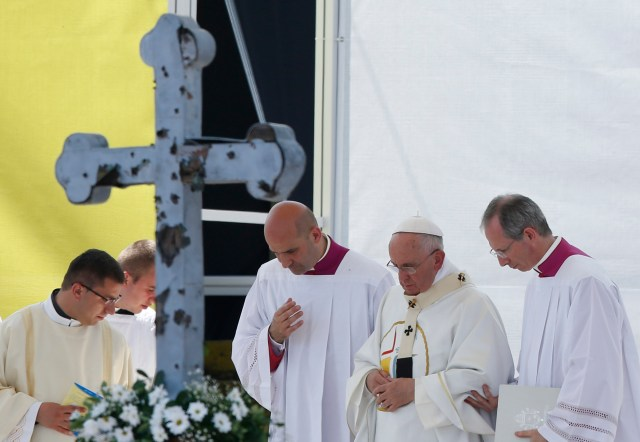 Celebrating Mass in Sarajevo's Kosevo Stadium, Pope Francis walks near a cross punctured by ammunition during the 1992-1995 Bosnian War. (CNS/Paul Haring)