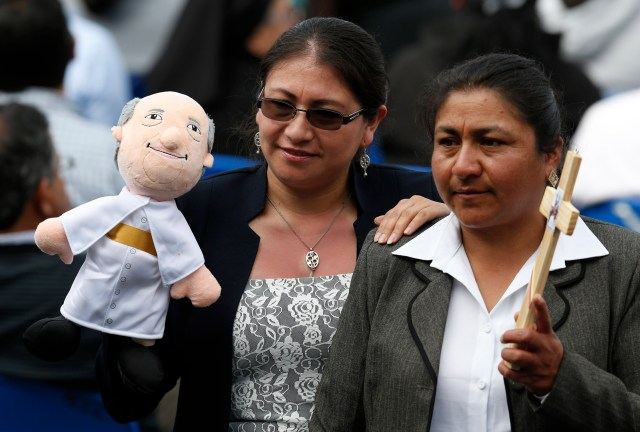 Women pose with a Pope Francis doll before the pope's meeting with representatives of schools and universities at the Pontifical Catholic University of Ecuador in Quito July 7.  (CNS/Paul Haring)