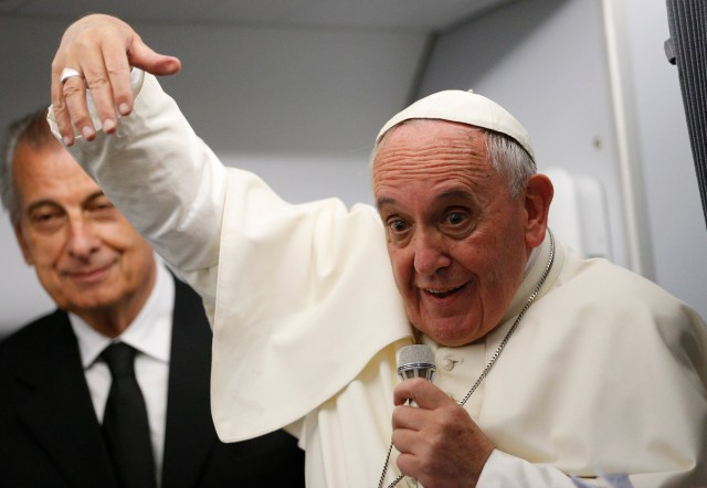 Pope Francis gestures as he answers questions from journalists aboard a papal flight last year. (CNS/Paul Haring)