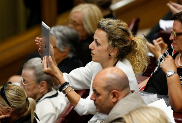 A woman takes a photo during a workshop on climate change and human trafficking attended by mayors from around the world in the synod hall at the Vatican July 21. Many mayors stayed a second day at the Vatican July 22 to discuss other topics. (CNS/Paul Haring)
