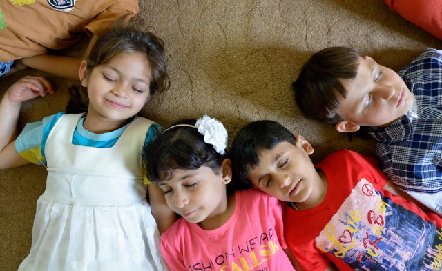 A group of children lies on the floor during an activity in the Youth Empowerment Center in Beit Hanoun, Gaza Strip. The program, designed to help children deal better with trauma and stress, is supported by Caritas Internationalis. (CNS/Paul Jeffrey)