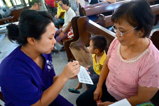 In this undated photo, Judy Chang provides an eye test to a woman in Kaohsiung City, Taiwan. A mission team of Chinese American Catholics from the San Francisco area also works in the Philippines and California's San Joaquin Valley. (CNS photo/courtesy Catholic San Francisco)