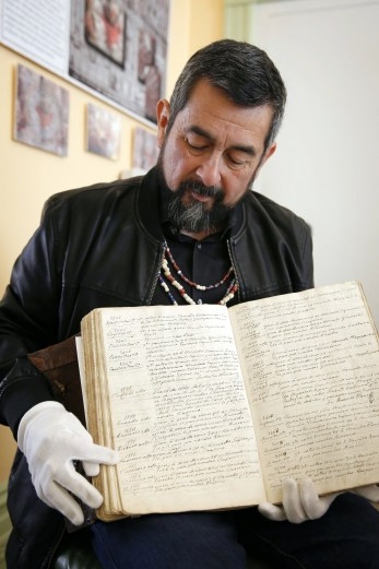 Andrew Galvan points to the entry for his great-great-great-great-grandfather in an early baptismal registry for Mission San Francisco de Asis, also known as Mission Dolores, in San Francisco. Listed as number 1552, the entry shows the Christian name given, Faustino. (CNS/Nancy Wiechec)