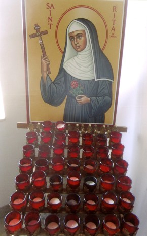 Artwork of St. Rita behind a candle rack at Our Lady of Redemption Church in Warren, Michigan. The Melkite parish in the Eastern tradition has moved locations to keep up with its members' changing lives. (CNS/Mark Pattison)