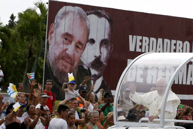 Pope Francis waves to people as he passes a billboard showing images of Cuba's former leader Fidel Castro and Cuban independence hero Jose Marti Sept. 19 in Havana. (CNS/Reuters)
