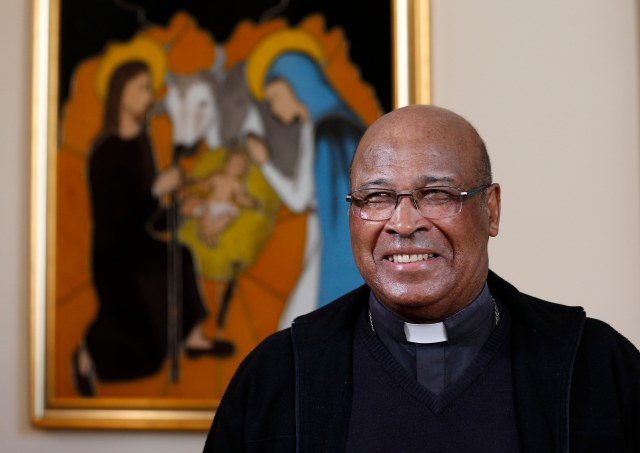Cardinal Wilfrid Napier of Durban, South Africa, is pictured near an image of the Holy Family after an interview with Catholic News Service in Rome Oct. 7. (CNS/Paul Haring)