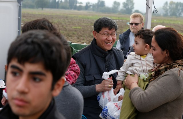 Cardinal Luis Antonio Tagle of Manila gives a food bag to a refugee family as they arrive at a transit camp in Idomeni, Greece, on the border of Macedonia Oct. 19. Thousands of refugees were arriving into Greece from Syria, Afghanistan, Iraq and other countries and then traveling further into Europe. (CNS/Paul Haring)