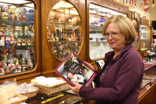 Joan Bittner, co-owner of the Polish Art Center in Hamtramck, Mich., holds a book on Polish Christmas traditions. The shop also sells items and fixings for celebrating the holiday, including Oplatki wafers and items to prepare the Wigilia meal on Christmas Eve. (CNS/Dan Meloy, The Michigan Catholic)