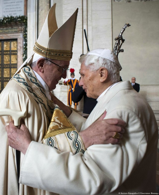 Pope Francis greets retired Pope Benedict XVI before opening the Holy Door in St. Peter's Basilica at the Vatican Dec. 8. (CNS photo/L'Osservatore Romano, handout via EPA)