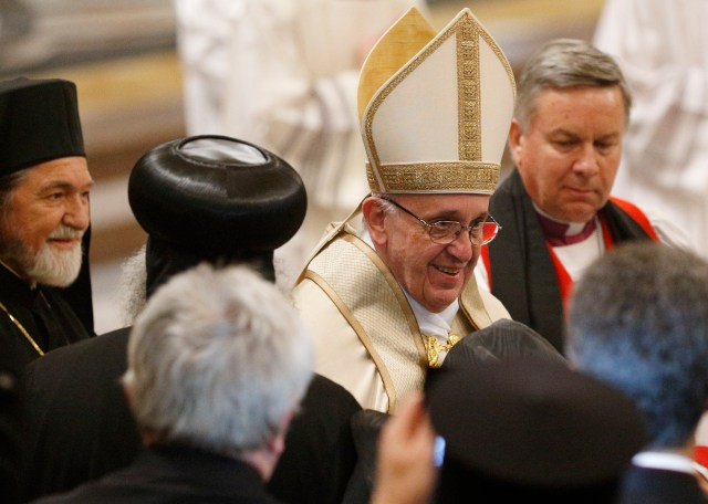 Pope Francis greets religious leaders as he leaves a prayer service at the Basilica of St. Paul Outside the Walls Jan. 25. The service concluded the Week of Prayer for Christian Unity. Also pictured is Orthodox Metropolitan Gennadios of Italy, left, and Anglican Archbishop David Moxon, right, the archbishop of Canterbury''s representative to the Vatican. (CNS/Paul Haring)