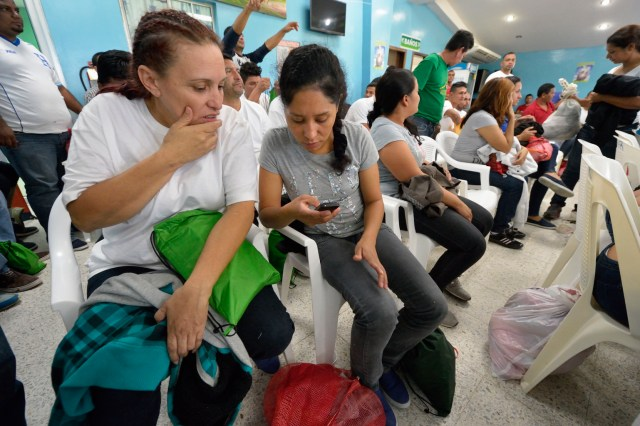 Honduran women deported from the United States use their phones to contact family and friends after they arrived at a church-run center in the San Pedro Sula airport Dec. 17. They were flown to the airport aboard a U.S. government flight, then bused to a remote section of the airport where the Catholic Church operates a Center for Attention to Returned Migrants. (CNS photo/Paul Jeffrey)