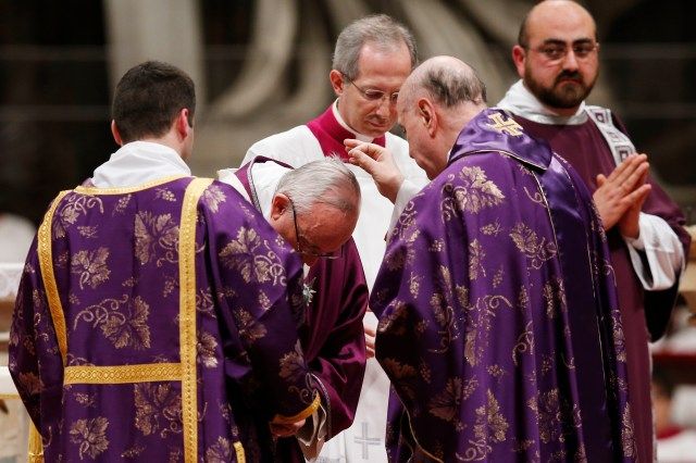 Cardinal Angelo Comastri, archpriest of St. Peter's Basilica, places ashes on Pope Francis' head during Ash Wednesday Mass in St. Peter's Basilica at the Vatican Feb. 10. (CNS/Paul Haring)