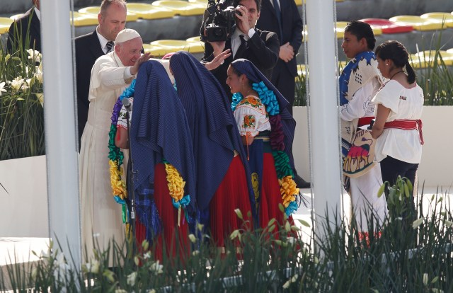 Pope Francis greets girls in traditional dress during a meeting with young people at the Jose Maria Morelos Pavon Stadium in Morelia, Mexico, Feb. 16. (CNS/Paul Haring)