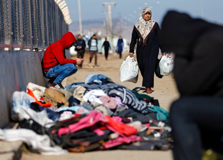 A refugee woman from Syria carries food while other displaced people sit near a border gate in Kilis, Turkey, Feb. 9. More than 30,000 people are stranded in northern Aleppo province after Turkish government forces closed border crossings. (CNS/EPA)