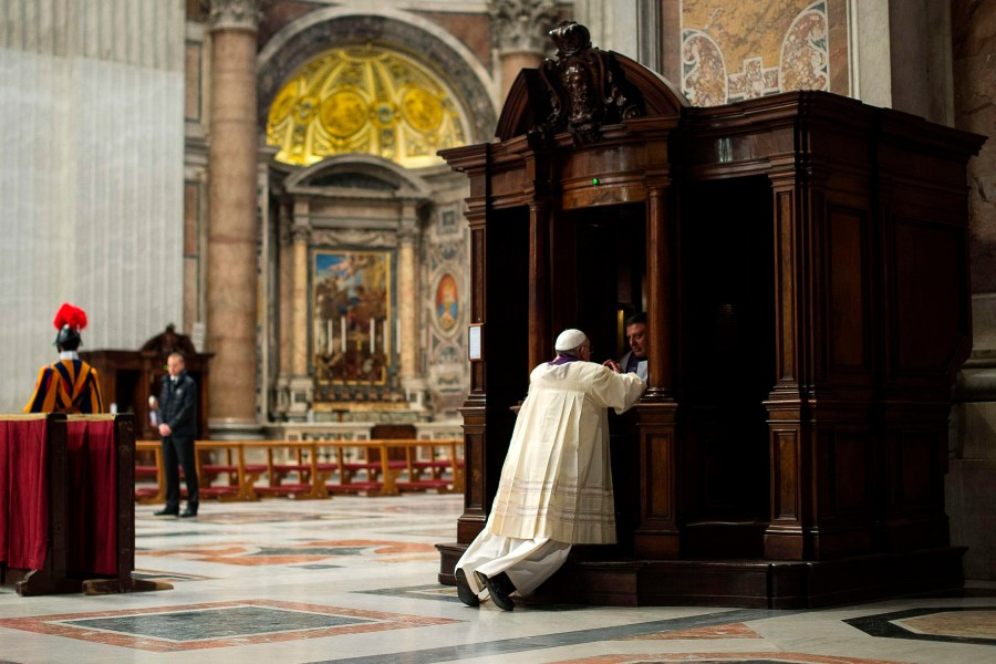 A priest hears confession from Pope Francis during a penitential liturgy in St. Peter's Basilica at the Vatican in this March 28, 2014, file photo. (CNS/L'Osservatore Romano via Reuters)