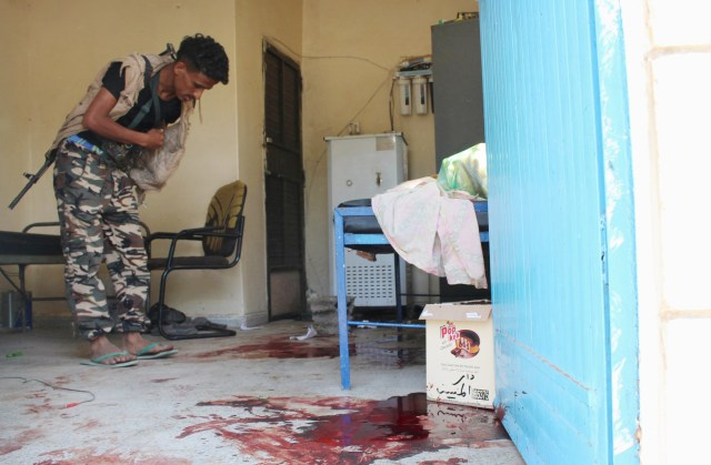 A pro-government militant inspects a room filled with blood after it was attacked by gunmen in Aden, Yemen, March 4. (CNS/Reuters)
