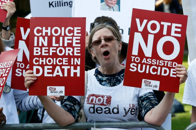 A demonstrator against assisted suicide joins a protest outside the Houses of Parliament in London last September. (CNS/Reuters)