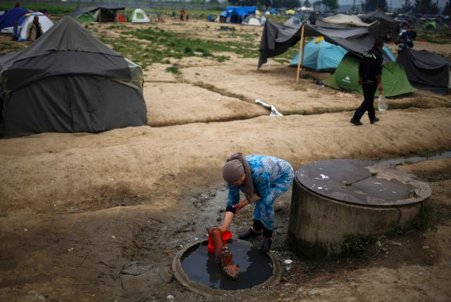 A woman collects water at a makeshift camp for migrants and refugees at the Greek-Macedonian border near the village of Idomeni, Greece. (CNS/Reuters)
