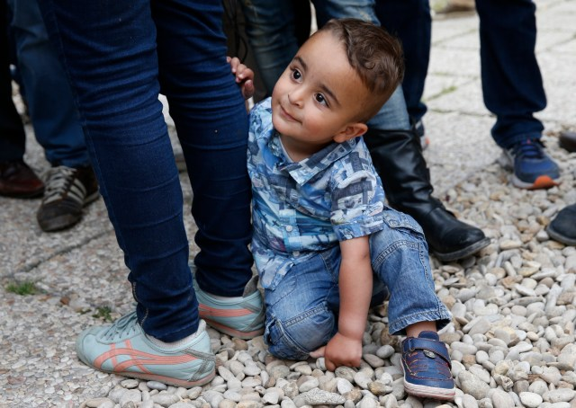 Syrian refugee Riad, 2, holds onto the leg of his mother, Nour, as she talks to media in Rome April 18. The boy, his mother and his father, Hasan, were among 12 Syrian refugees that Pope Francis brought to Rome from a refugee camp in Greece. (CNS/Paul Haring)