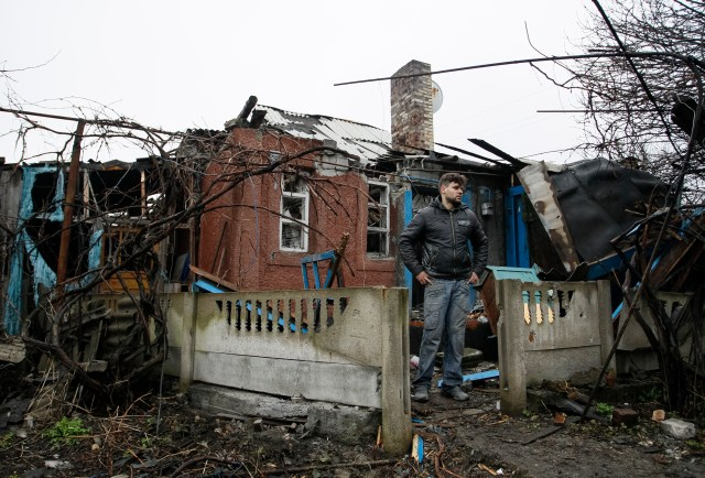 A man stands in front his damaged house after shelling March 24 in the Ukrainian town of Makeevka. (CNS/EPA)