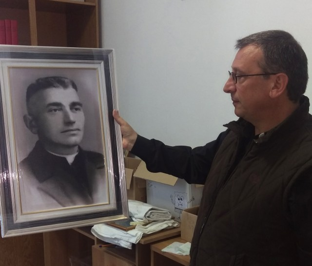 Franciscan Brother Vincenzo Foca holds a photo of Father Luigj Prendushi in Shkoder, Albania. Father Prendushi was killed in Albania under that country's former atheist regime and Brother Vincenzo has spent the last 24 years locating bodies of Catholics in Albania, some of whom, like Father Prendushi, are on Pope Francis' list of martyrs. (CNS/James Martone)