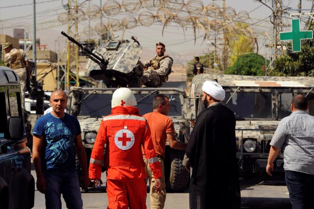 Lebanese army soldiers patrol as a Red Cross member walks near the site where suicide bomb attacks took place June 27 in the village of Qaa. Four suicide bombers attacked the predominantly Christian village in northeast Lebanon near the border with Syria, killing at least five people in addition to themselves. (CNS Reuters)