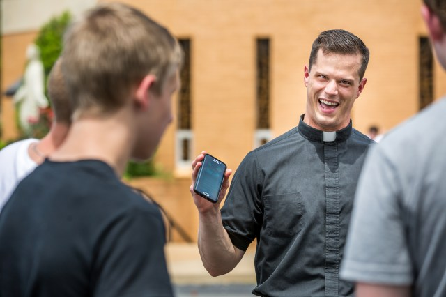 Father David Miloscia of Assumption Parish in St. Louis shows young people the game Pokemon Go on his cellphone as they chase Pokemon stops around the church grounds July 14. (CNS/Lisa Johnston, St. Louis Review)