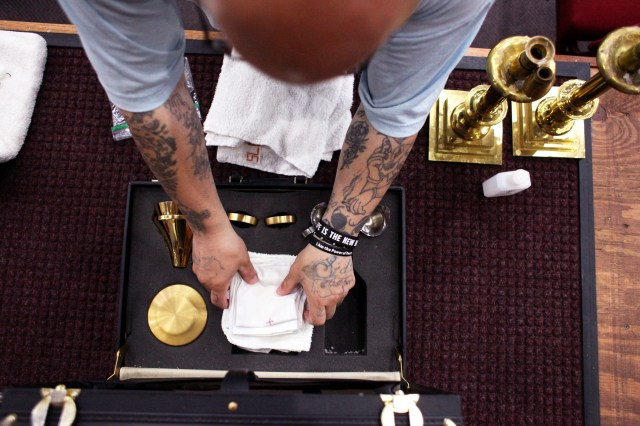 An inmate puts away the items used on the altar following a a June 9 Mass at the Ellsworth Correctional Facility in Kansas. (CNS photo/Karen Bonar, The Register)