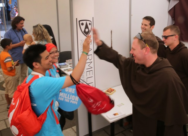 Carmelite Brother Kevin Kelly of the Chicago province gives a high five to pilgrims from Indonesia at the World Youth Day evangelization center July 29 in Krakow, Poland. (CNS/Bob Roller)