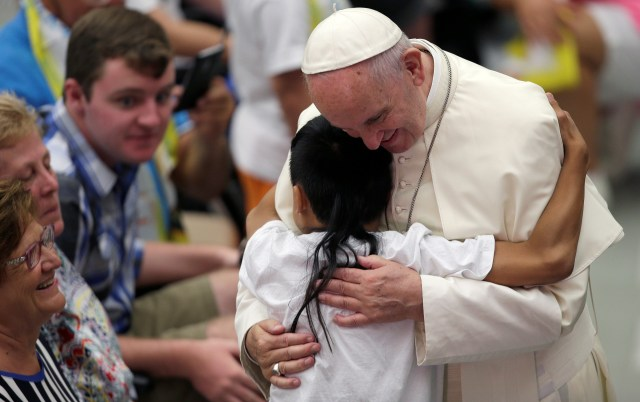 A sick child greets Pope Francis during his general audience in Paul VI hall at the Vatican Aug. 3. (CNS/Reuters)