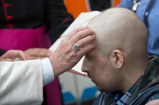 Pope Francis administers the sacrament of confirmation to Giuseppe Chiolo, 16, in St. Peter's Square during a Year of Mercy general audience at the Vatican Sept. 10. The young man is being treated in the oncology ward of a Florence hospital. (CNS/L'Osservatore Romano)