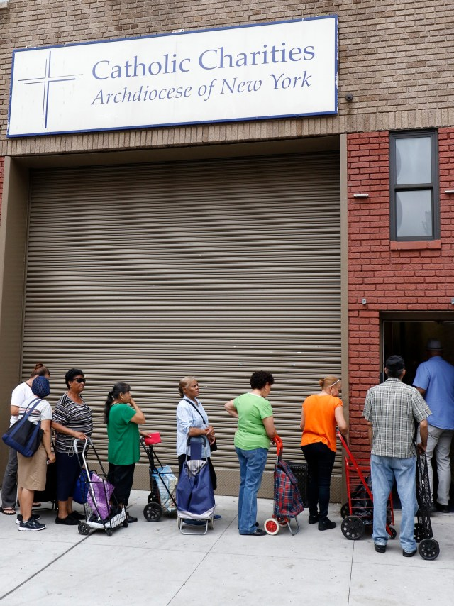 People wait to enter a food pantry at Catholic Charities of the Archdiocese of New York's community center in the South Bronx July 14. Both the Democrats and the Republicans address economic issues in the opening pages of their respective parties' platforms, an indication of how seriously they take economic policy in its potential appeal to voters this election year. (CNS photo/Gregory A. Shemitz)