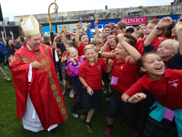 Archbishop Bernard A. Hebda of St. Paul and Minneapolis greets students from St. Mark School in St. Paul, Minn., after celebrating the Mass of the Holy Spirit Sept. 22 at a baseball park in downtown St. Paul. (CNS photo/Dave Hrbacek, The Catholic Spirit)
