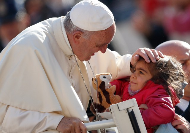 Pope Francis greets a girl holding a stuffed animal during his general audience in St. Peter's Square at the Vatican Oct. 19. (CNS/Paul Haring)