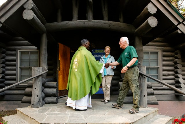 Father Lucas Kazimiro Simango greets Massgoers as they enter the log Chapel of the Sacred Heart in Grand Teton National Park in Wyoming. (CNS/Nancy Wiechec)