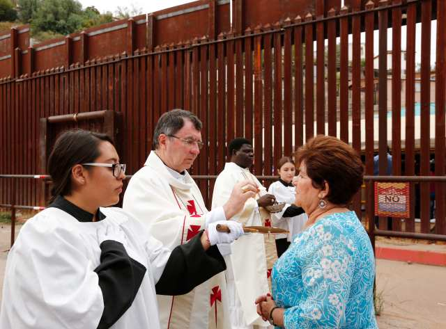 Archbishop Christophe Pierre, apostolic nuncio to the United States, gives Communion during Mass at the international border in Nogales, Ariz., Oct. 23. Dioceses Without Borders, an effort of Mexico's Nogales Diocese and the U.S. dioceses of Phoenix and Tucson, Ariz., organized the liturgy celebrated on both sides of the U.S.-Mexico border. (CNS/Nancy Wiechec)