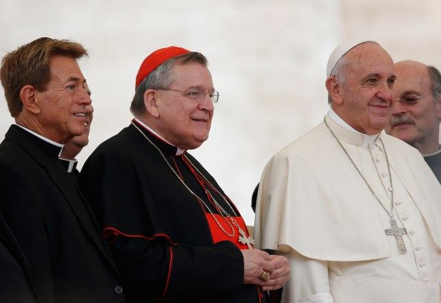 U.S. Cardinal Raymond L. Burke, patron of the Knights and Dames of Malta, center left, and a group of priests pose with Pope Francis during a papal general audience in St. Peter's Square at the Vatican last year. (CNS file/Paul Haring)