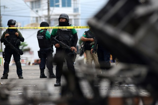 Police officers guard the municipal building in Catemaco, Mexico, Nov. 14 after it was set on fire following the disappearance of Father Jose Luis Sanchez Ruiz. (CNS/Reuters)