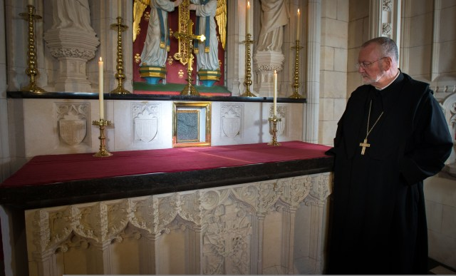 Benedictine Abbot David Charlesworth of England's Buckfast Abbey looks at the encased hair shirt worn by St. Thomas More. The shirt is now on permanent display at the abbey. (CNS/Luke Michael Davies, courtesy Buckfast Abbey Media Studios)