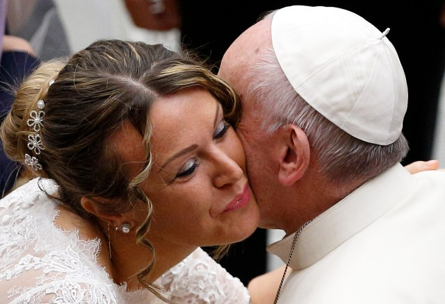 A newly married woman wearing her wedding dress kisses Pope Francis during his general audience in Paul VI hall at the Vatican Nov. 30. (CNS/Paul Haring)